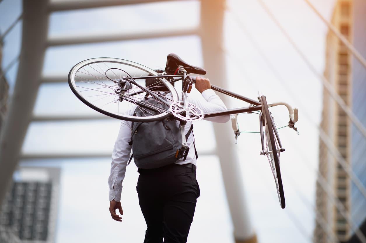 a man carrying a cummuter bike