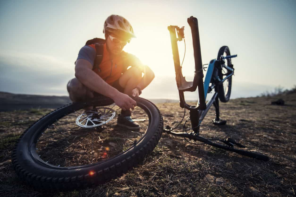 a man fixing his bike wheel