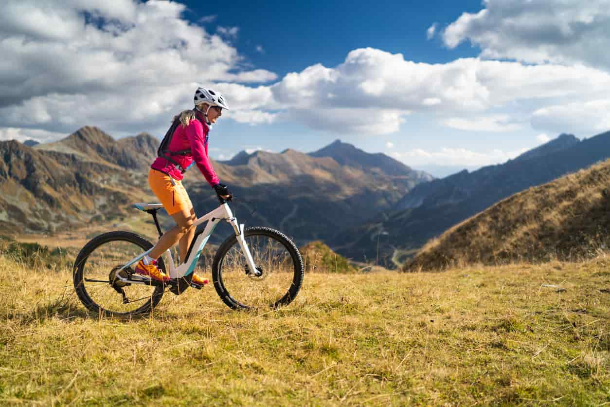 a woman riding her bike on a field