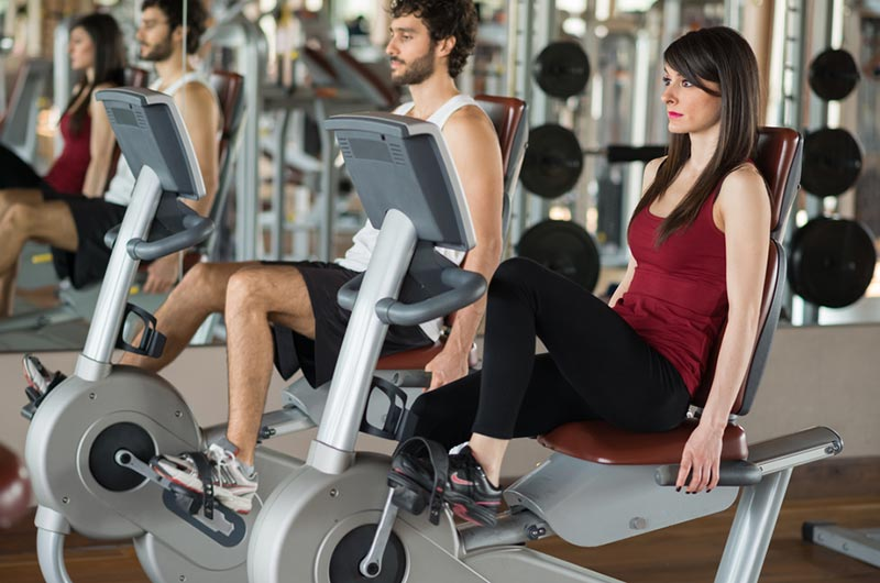 man and woman using exercise recumbent bikes