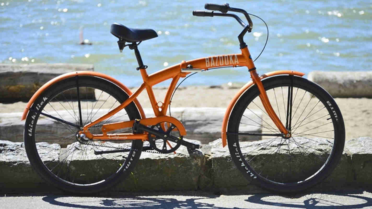 orange cruiser bike parked near the beach